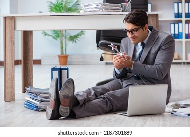 Young handsome employee sitting on the floor in the office