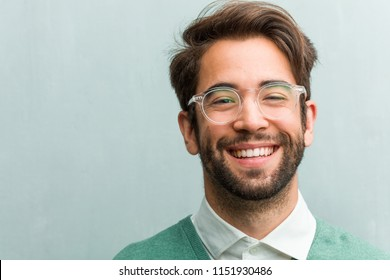 Young handsome entrepreneur man face closeup cheerful and with a big smile, confident, friendly and sincere, expressing positivity and success
