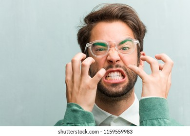 Young handsome entrepreneur man face closeup very angry and upset, very tense, screaming furious, negative and crazy