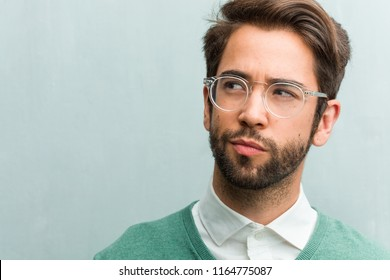 Young handsome entrepreneur man face closeup doubting and confused, thinking of an idea or worried about something