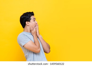Young handsome excited Asian man with hands covering mouth isolated on yellow studio background with copy space