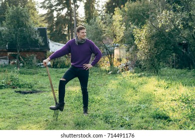 A young handsome farmer. The mood is very strong. Purple sweater. Cart with hay. Sunset light. Autumn mood. forks