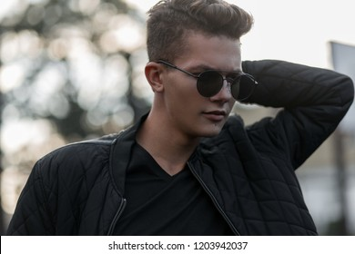 Young handsome fashion man with stylish sunglasses in black trendy bomber jacket outdoors