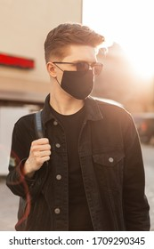 Young handsome fashion man with sunglasses with backpack and wearing a face pollution mask to protect himself from the coronavirus walking in city at sunset. Stylish guy in denim black clothes