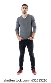 Young handsome fashion model in gray shirt with hands in pockets looking at camera. Full body length portrait isolated over white studio background.