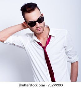 young handsome fashion model man posing in white shirt with red tie