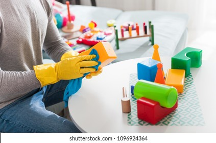 Young handsome father cleaning toys and table after playing with his child at home