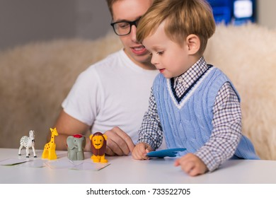 The young handsome father with his little happy son playing by toy animals indoors