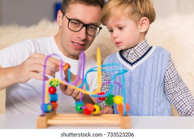 The young handsome father with his little cute son playing by developing toy indoors