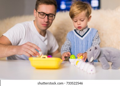 The young handsome father sitting with his little cute son at the table and playing by  toys indoors