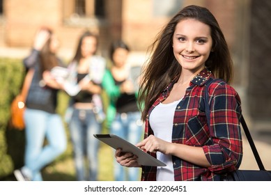 Young handsome female student at the college, outdoors. Her classmates in the background.