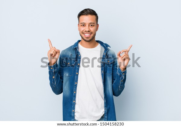 Young handsome filipino man indicates with both fore fingers up showing a blank space.