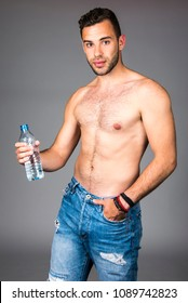 young handsome fit man drinks water / male model with bottle of water