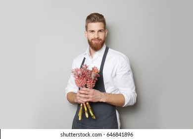 Young handsome florist with beautiful exotic pineapples on grey background