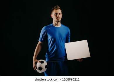 Young handsome football player soccer holds ball and white blank on black background studio. blue outfit. Stylish haircut and bristles.
