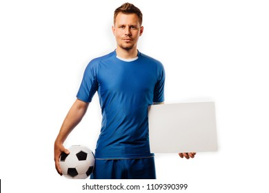 Young handsome football player soccer holds ball and white blank on white isolated background studio. blue outfit. Stylish haircut and bristles.