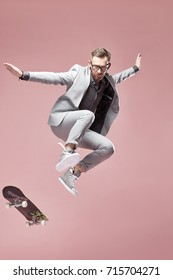 Young handsome funny man with glasses, brown hair and beard, wearing light grey suit and sneakers, jumping with the skateboard on light pink background