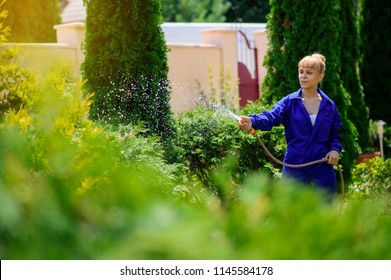 Young handsome  gardener girl is watering the garden with the hose