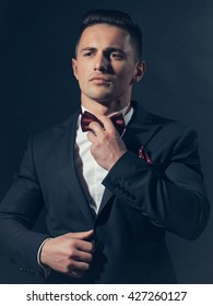 young handsome gentleman in fashion black suit white shirt and bow tie in studio