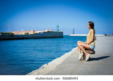 Young handsome girl sitting next sea port looking horizon -Soft saturated filter with vintage vignette editing