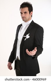 A young and handsome groom in tuxedo lending out a hand towards camera.