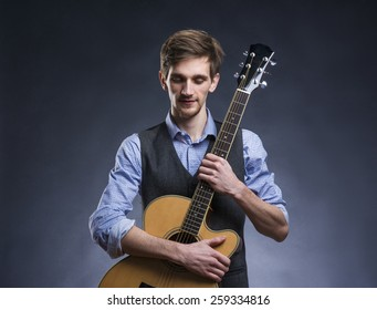 Young handsome guitar player. Studio shot on black background.