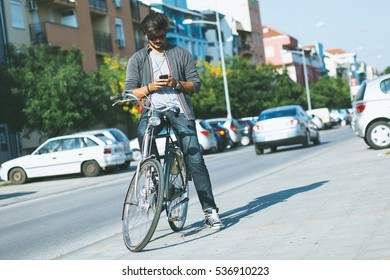 Young handsome guy with a bicycle on street looking at mobile phone.