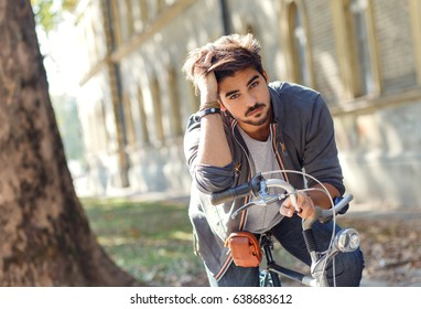 Young handsome guy with a bicycle on street.