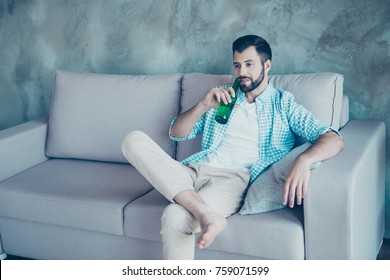 Young handsome guy with bristle drinking beer, putting one leg on another, relaxing after hard day at home, sitting on the couch, watching his favorite tv program
