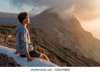 Young handsome guy enjoying of beautiful landscape view, sitting on the roadside on the mountain hill.