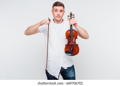 A young handsome guy holds a violin in his hands and does not understand what to do with it isolated on a gray background
