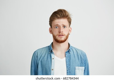 Young handsome guy looking at camera naively hopefully over white background.