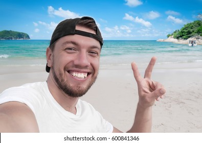 Young handsome guy making selfie on the beach