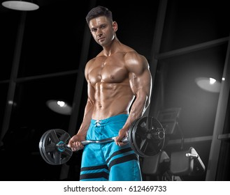 Young handsome guy with a naked torso doing exercises in the gym