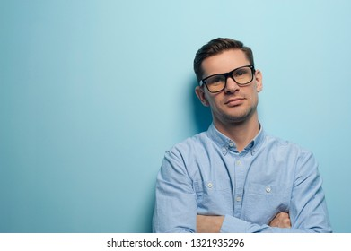 Young handsome guy office manager or businessman in formal wear and eyeglasses looking to the camera. Place for your advertising