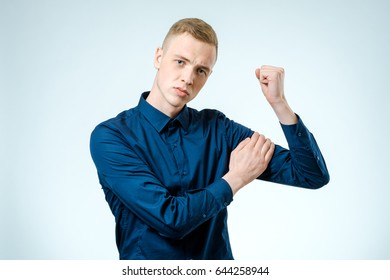 Young handsome guy pointing at his biceps showing how strong he is. Isolated on white
