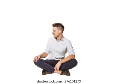 Young and handsome guy in shirt and trousers sitting on a white background