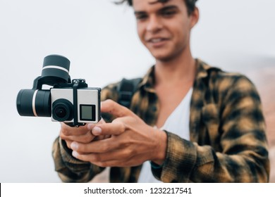 Young handsome guy shoots a video on an action camera on steadicam, standing outdoors.