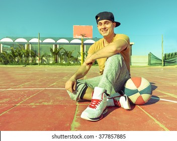 Young handsome guy sitting on basketball camp near the beach - Happy man take a rest after playing basket - Healthy lifestyle sport recreation concept - Vintage retro filter look