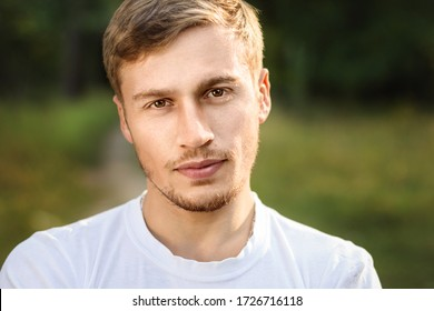 Young handsome guy with a sporty physique in a white T-shirt in a meadow on summer nature. Young serious man. Outdoor fashion male portrait.