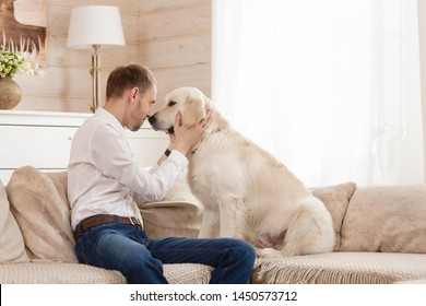Young handsome guy teaches his big dog to the rules sitting on the sofa in the living room of his country house. Dog training concept