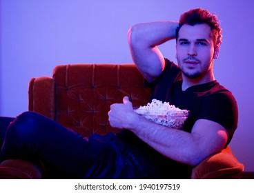 Young handsome guy watching exciting feature movie having popcorn.