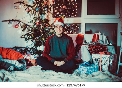 Young handsome happy man in a cap sits by Christmas tree next to the window at night