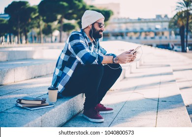 Young handsome happy man watching online webinar course in popular website using digital tablet and earphones.  Positive male student spending time listening to favorite music and audio book via app