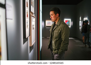 A young, handsome and healthy Chinese Asian man views works of art inside a private art gallery.