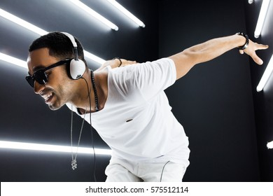 young handsome hipster man listening to music on headphones, smiling happy, white t-shirt, disco night club, having fun, hip hop style, positive mood, cool face expression