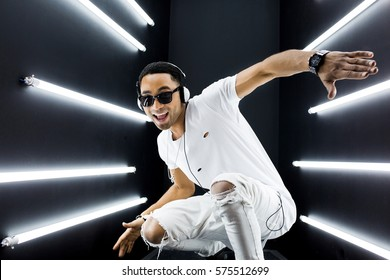young handsome hipster man listening to music on headphones, smiling happy, white apparel, disco night club, having fun, hip hop style, positive mood, face expression, dancing
