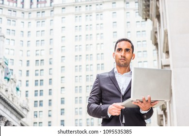 Young Handsome Hispanic American Businessman traveling, working in New York, wearing white wired earphone, standing on street by high old business building, listening music, working on laptop computer