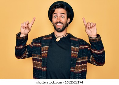 Young handsome hispanic bohemian man wearing hippie style and boho hat smiling amazed and surprised and pointing up with fingers and raised arms.