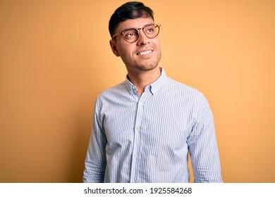 Jeune homme d'affaires hispanique très charmant portant des lunettes d'oiseau sur fond jaune, regardant de l'autre côté, sourire au visage, expression naturelle. Rire confiant.